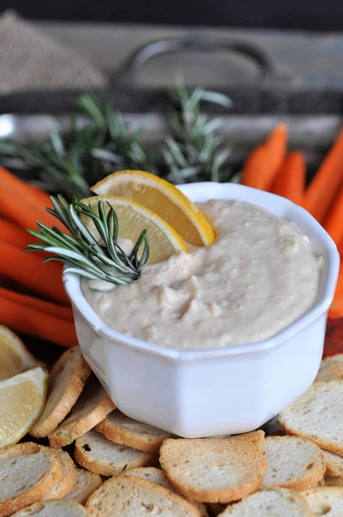 hummus in a white bowl, with lemon and rosemary, easy vegan appetizers, baked bruschetta
