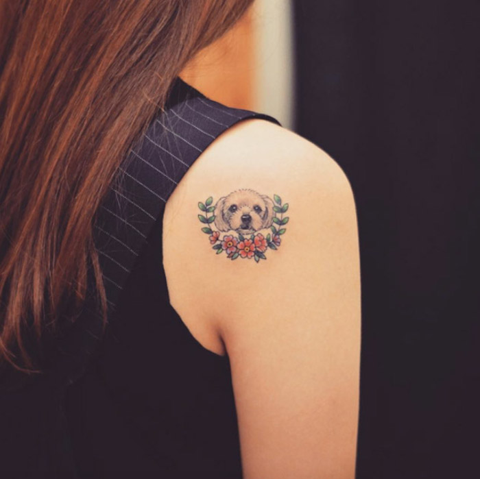 upper arm tattoos, dog with flowers, shoulder tattoo, black top, brown hair