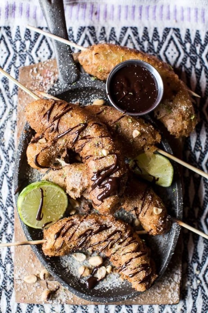 fried bananas, with melted chocolate, sliced lime, vegan appetizers, wooden board