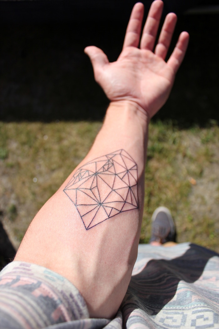 geometrical forearm tattoo, arm tattoos for girls, patterned blouse, green grass