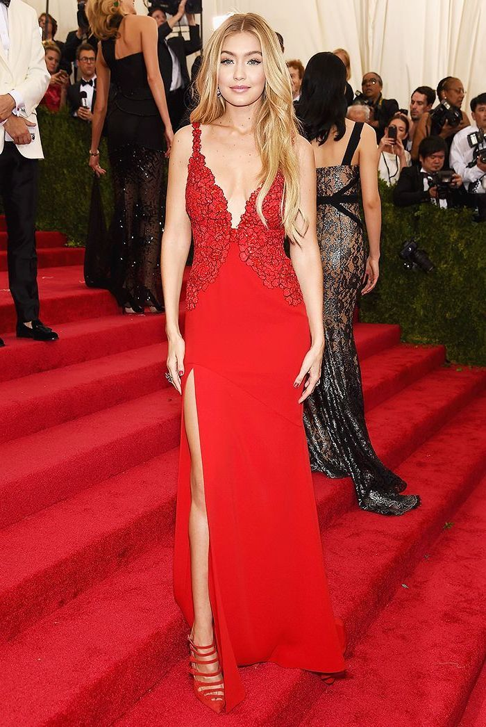 met gala, gigi hadid, wearing a long red dress, with long blonde wavy hair, red velvet heels