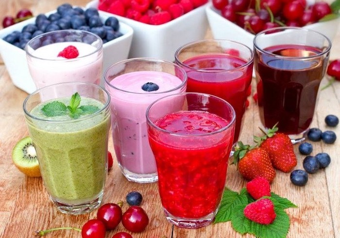 tall glasses, filled with smoothies, made with different ingredients, strawberry banana smoothie, different fruits