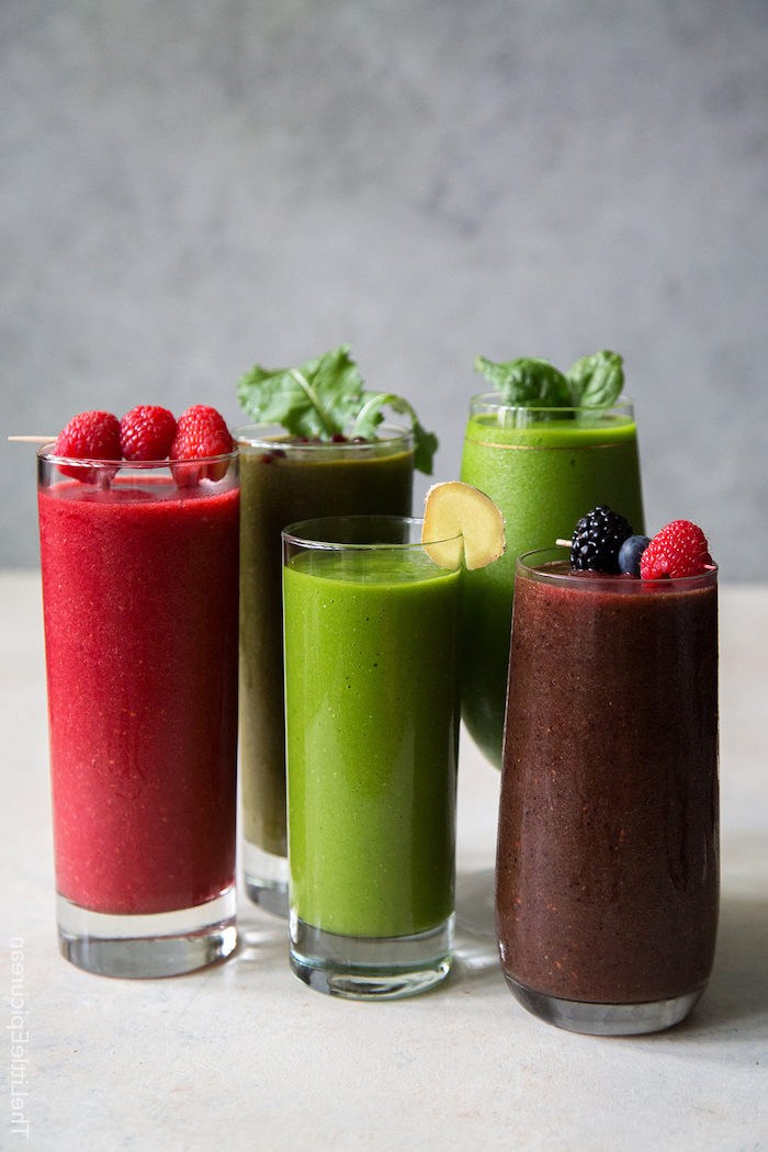 tall glasses, filled with colourful smoothies, strawberry banana smoothie, made with different ingredients