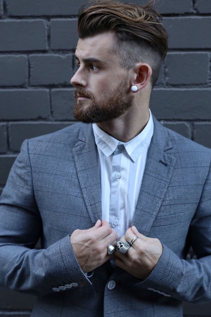 grey brick wall, grey jacket, white shirt, brown hair, cool haircuts for men, silver rings