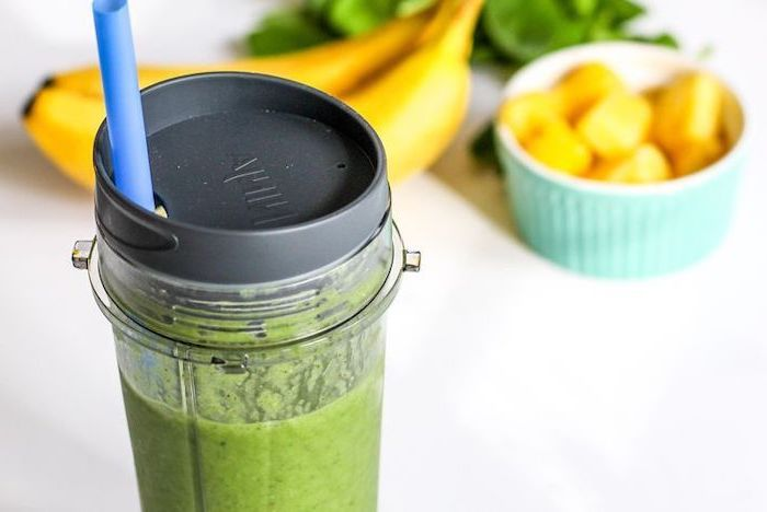 breakfast smoothie recipes, in a glass bottle, with blue straw, mango and banana