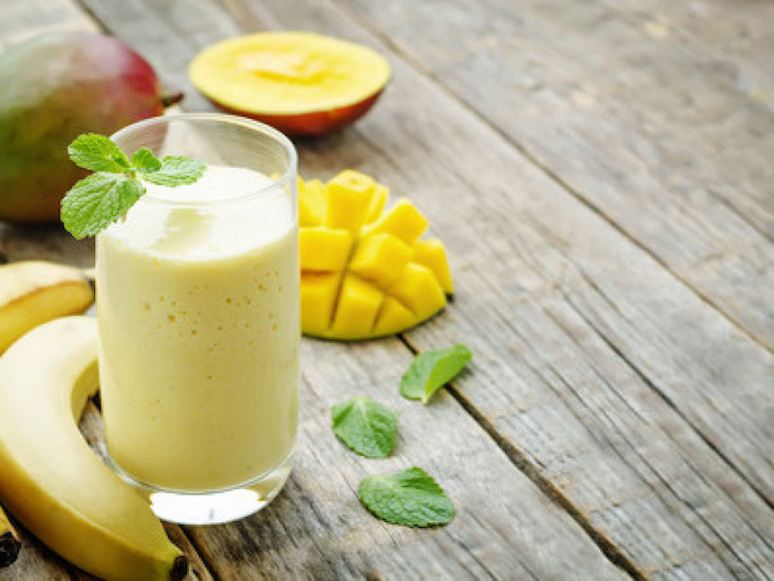 mango slices, bananas on the side, mint leaves, breakfast smoothie recipes, on a wooden table