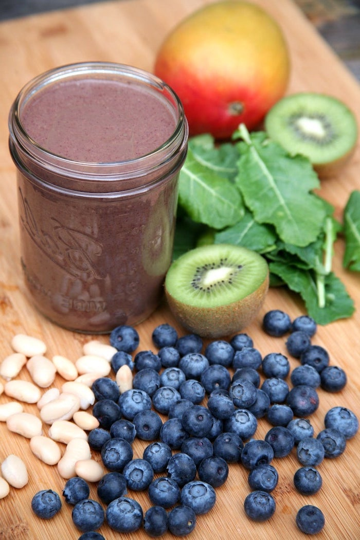 protein smoothie recipes, kiwi slices, berries and peanuts, apple and spinach, on a wooden board
