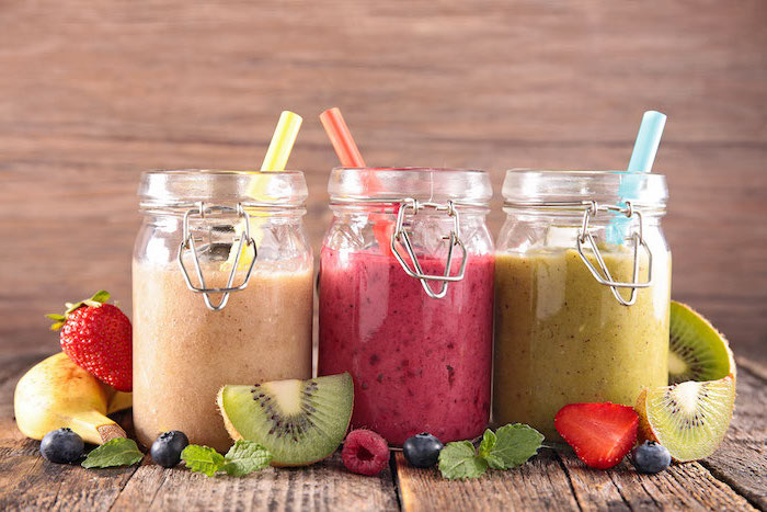 three jars, filled with different smoothies, healthy smoothie recipes, scattered fruit slices around