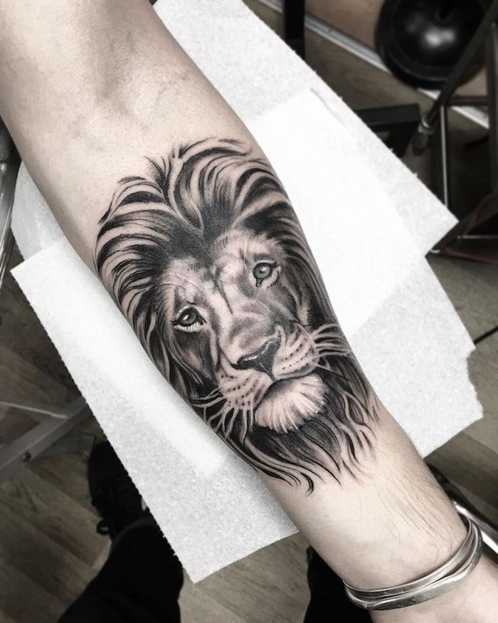 lion head, hand on white paper, silver bracelet, forearm sleeve tattoo