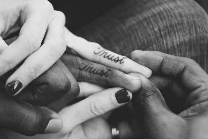 trust inside finger tattoos, black nail polish, black and white photo, unique couple tattoos