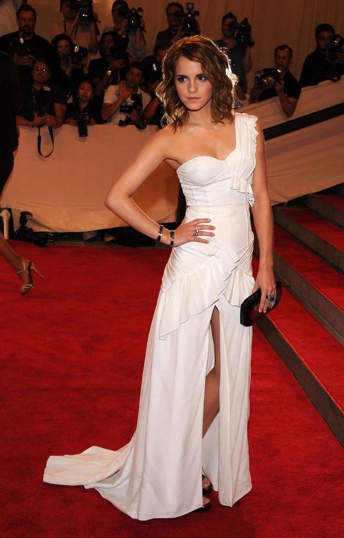 met gala red carpet, emma watson, long white dress, short brown curly hair, black clutch bag