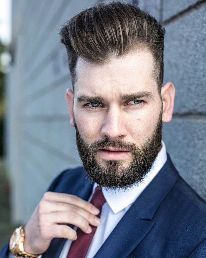 navy suit, white shirt, red burgundy tie, medium haircuts for men, brick wall, gold watch, brown hair and beard