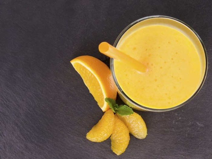 sliced oranges, how to make a mango smoothie, yellow straw, black countertop