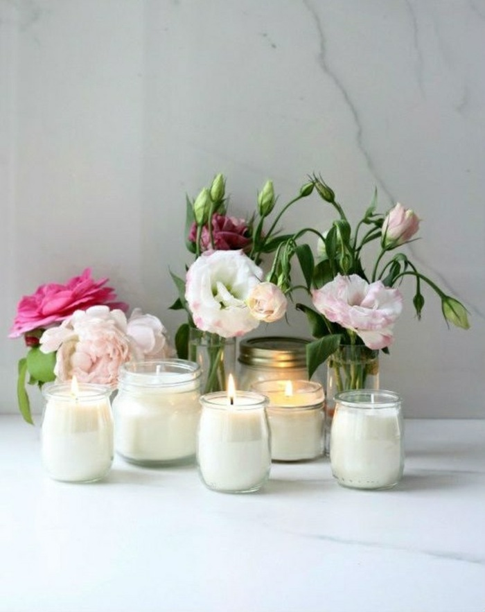 small peony flower bouquets, mason jar candles, small jars, on a marble countertop