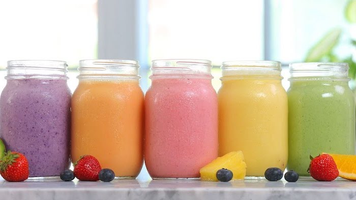 fruit slices, healthy smoothie recipes, different ingredients, in large jars
