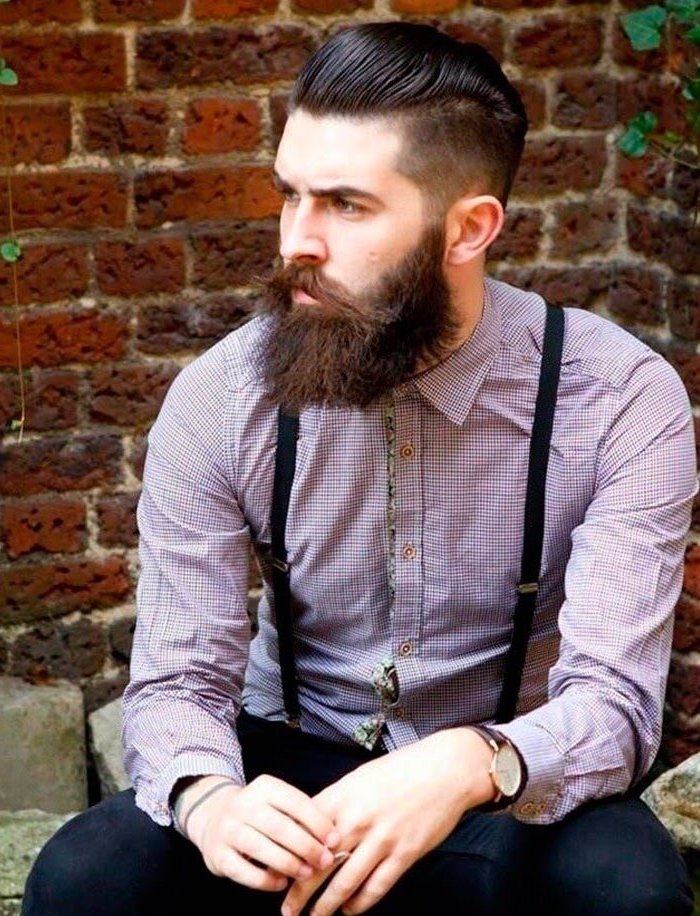 brick wall, modern haircuts for men, purple shirt, black suspenders, brown hair and beard