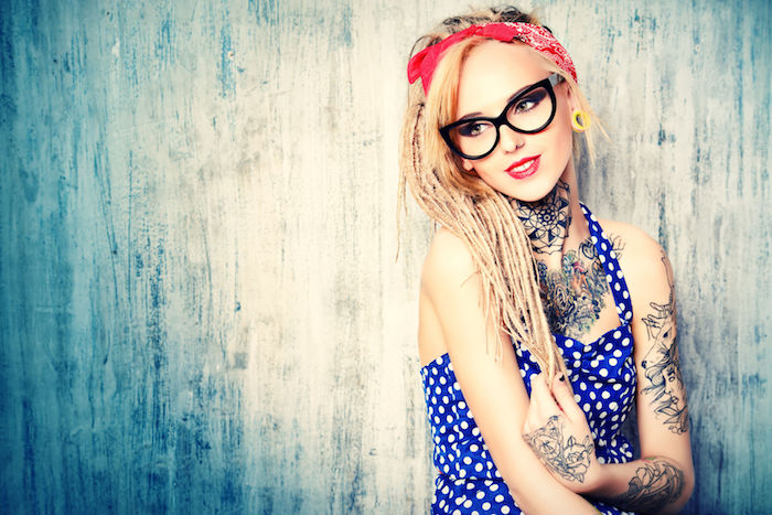 red bandana, small tattoos with meaning, blue dress, with white dots, colourful arm and chest tattoos