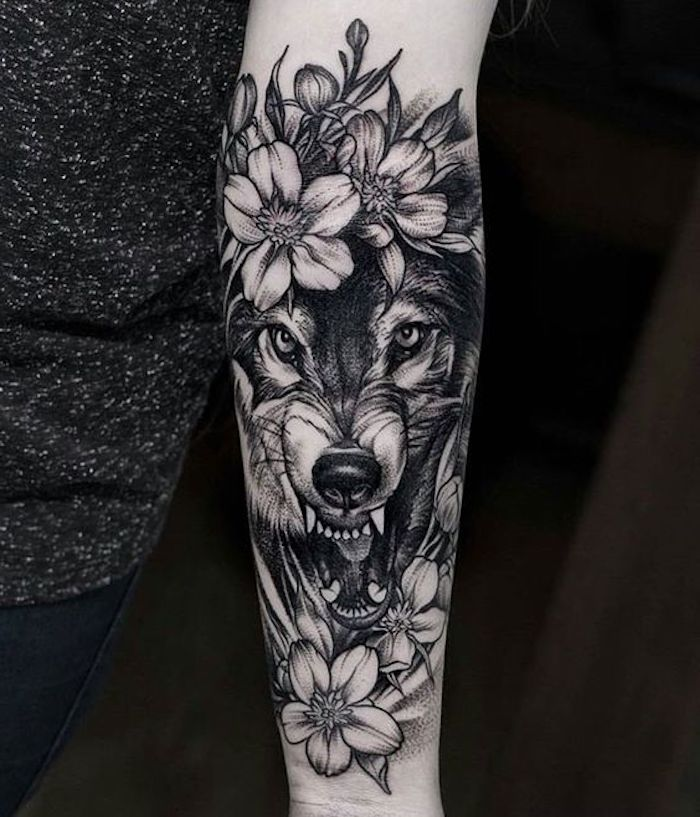 roaring wolf, surrounded by flowers, small tattoos with meaning, grey top