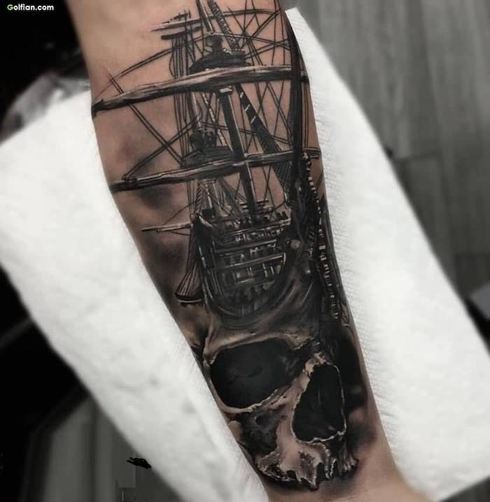 sailing ship, skull underneath, cool arm tattoos, hand on white paper