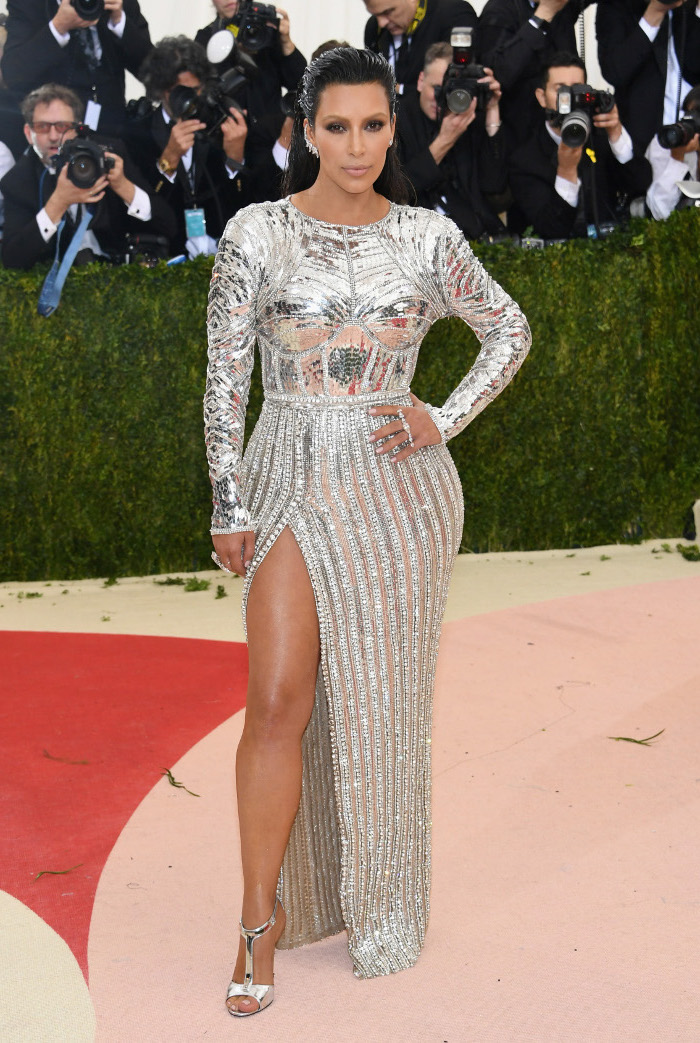 kim kardashian, long silver metallic dress, black hair, silver sandals, what is the met gala