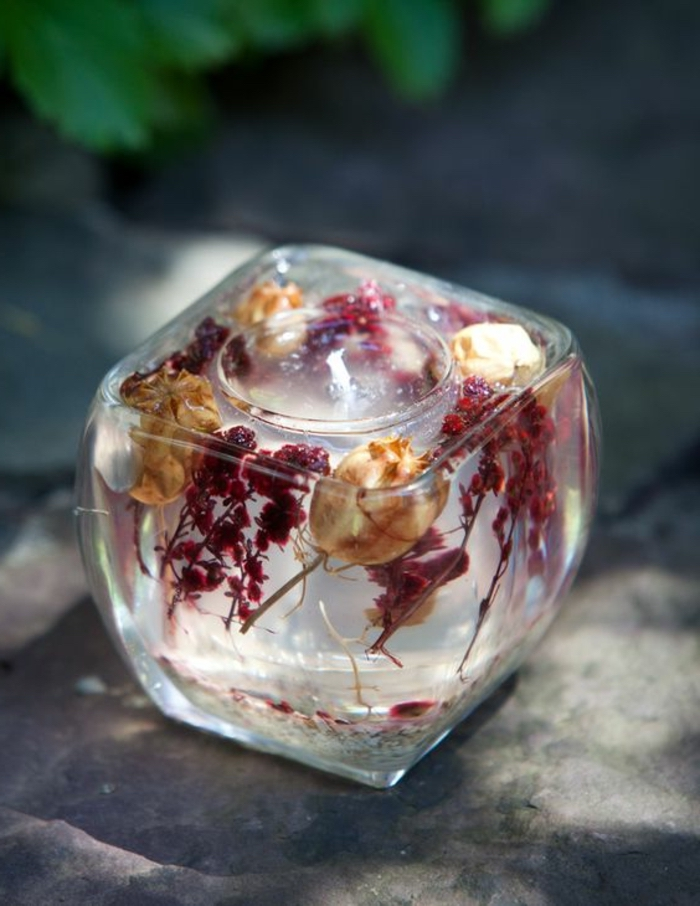 small round glass, inside a large square vase, filled with candle wax, dried flowers, how to make candles