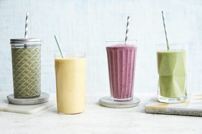 tall glasses, filled with different smoothies, ceramic coasters, peanut butter banana smoothie