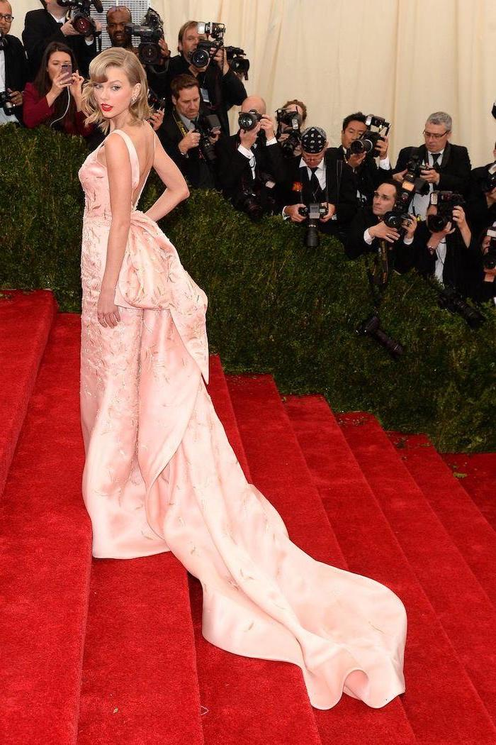 met costume institute, taylor swift, light pink dress, long train, large bow on the back, on the red carpet