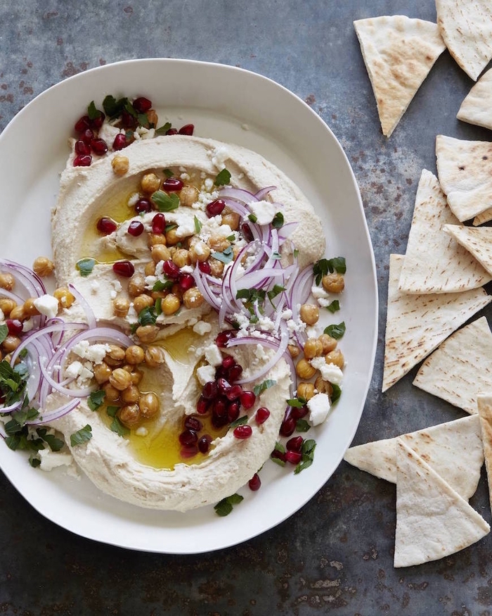 vegetarian super bowl recipe, hummus with chickpeas, onion and pomegranate, in a white plate