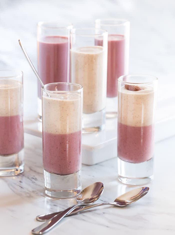 layered smoothies, in tall glasses, two spoons, peanut butter and banana smoothie, marble countertop