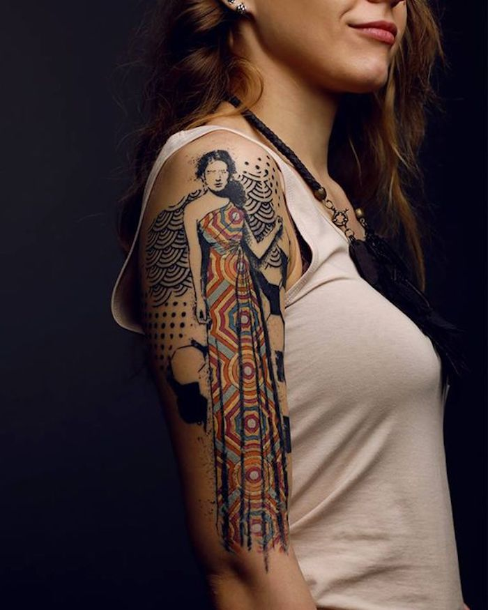 woman with a long colourful dress, shoulder tattoo, tattoos with deep meaning, white top, black background