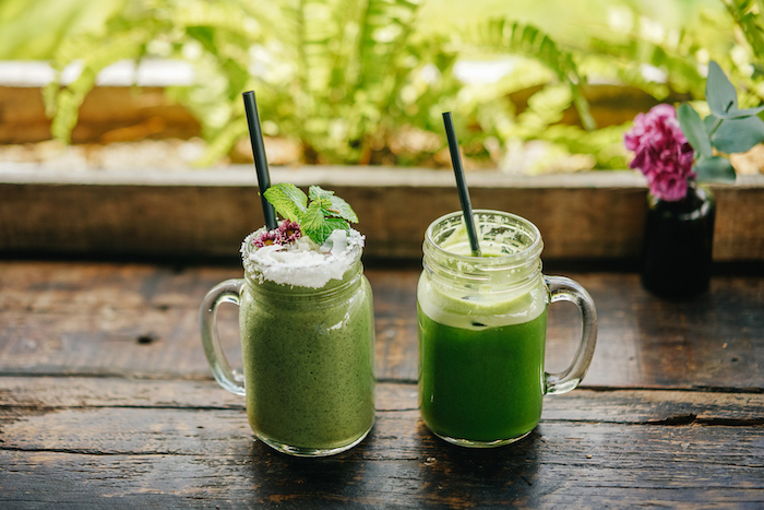 black straws, how to make a green smoothie, on a wooden table, flowers in the background