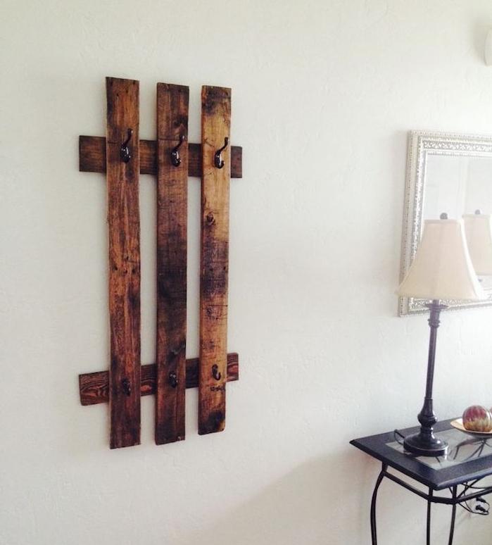 exemple de porte manteau original en planches de bois brut avec des accroches metalliques noires
