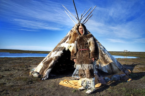 Inuit person in front of teepee