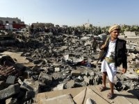 epaselect epa04679313 An armed member of Houthi militia (R) keeps watch as people gather beside vehicles which were allegedly destroyed by a Saudi air strike, in Sana'a, Yemen 26 March 2015. Saudi Arabia and other Gulf states launched air strikes against Houthi rebels which have taken over large parts of Yemen, attacking the Sana'a military Airport and Jiraf area, a Houthi stronghold. The strikes were 'in support of the people of Yemen and their legitimate government,' Saudi Arabia's Washington ambassador Adel al-Jubeir said. The military operation by a 'coalition of over 10 countries' was in response to an appeal from embattled Yemeni President Abdo Rabbo Mansour Hadi, al-Jubeir said.  EPA/YAHYA ARHAB