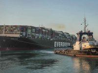 """In this photo released by Suez Canal Authority, the Ever Given, a Panama-flagged cargo ship, is pulled by one of the Suez Canal tugboats, in the Suez Canal, Egypt, Monday, March 29, 2021. Engineers on Monday """"partially refloated """" the colossal container ship that continues to block traffic through the Suez Canal, authorities said, without providing further details about when the vessel would be set free. (Suez Canal Authority via AP)"""