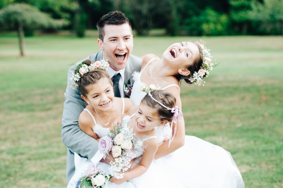 Groom hugging the flower girls and laughing. Photo by Ardita Kola Photography.