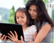 pretty little girl reading on an ipad with her mom