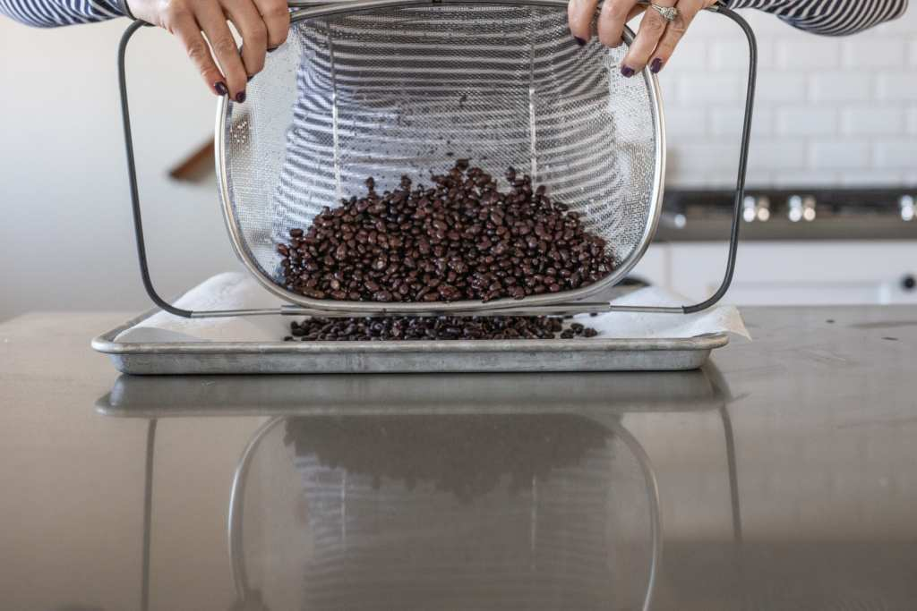 Woman pouring black beans onto baking sheet