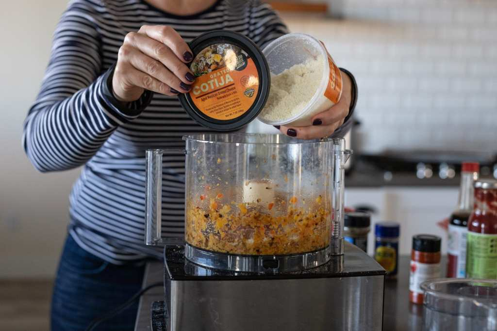 woman adding cotija to foodprocessor for burger