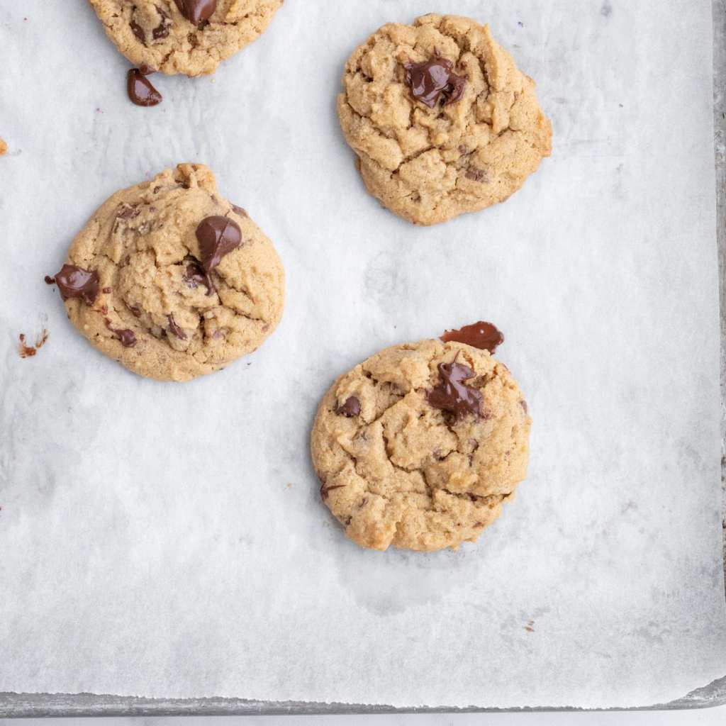 peanut butter chocolate chunk cookies on parchment lined baking sheet