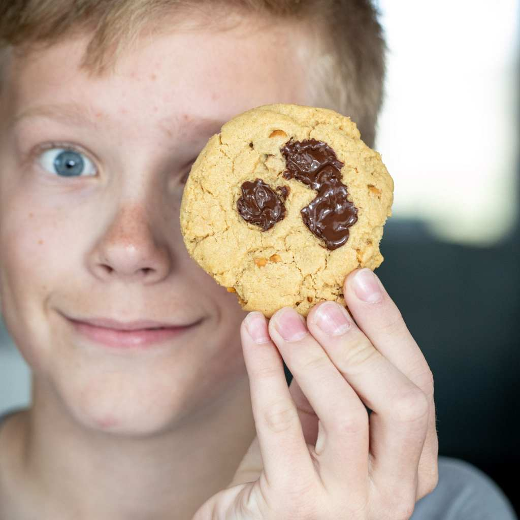 boy holding peanut butter chocolate chunk cookie