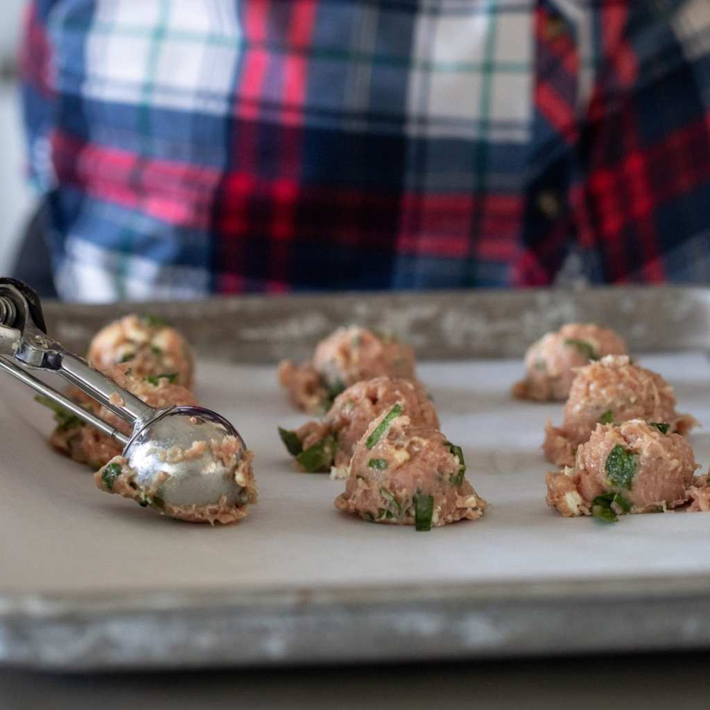 scooping meatballs onto parchment lined baking sheet