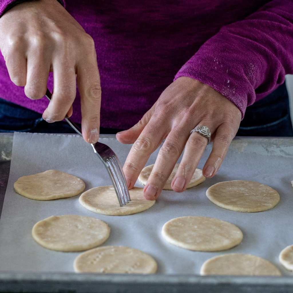woman pricking pie circles on parchment lined baking sheet in preparation for baking