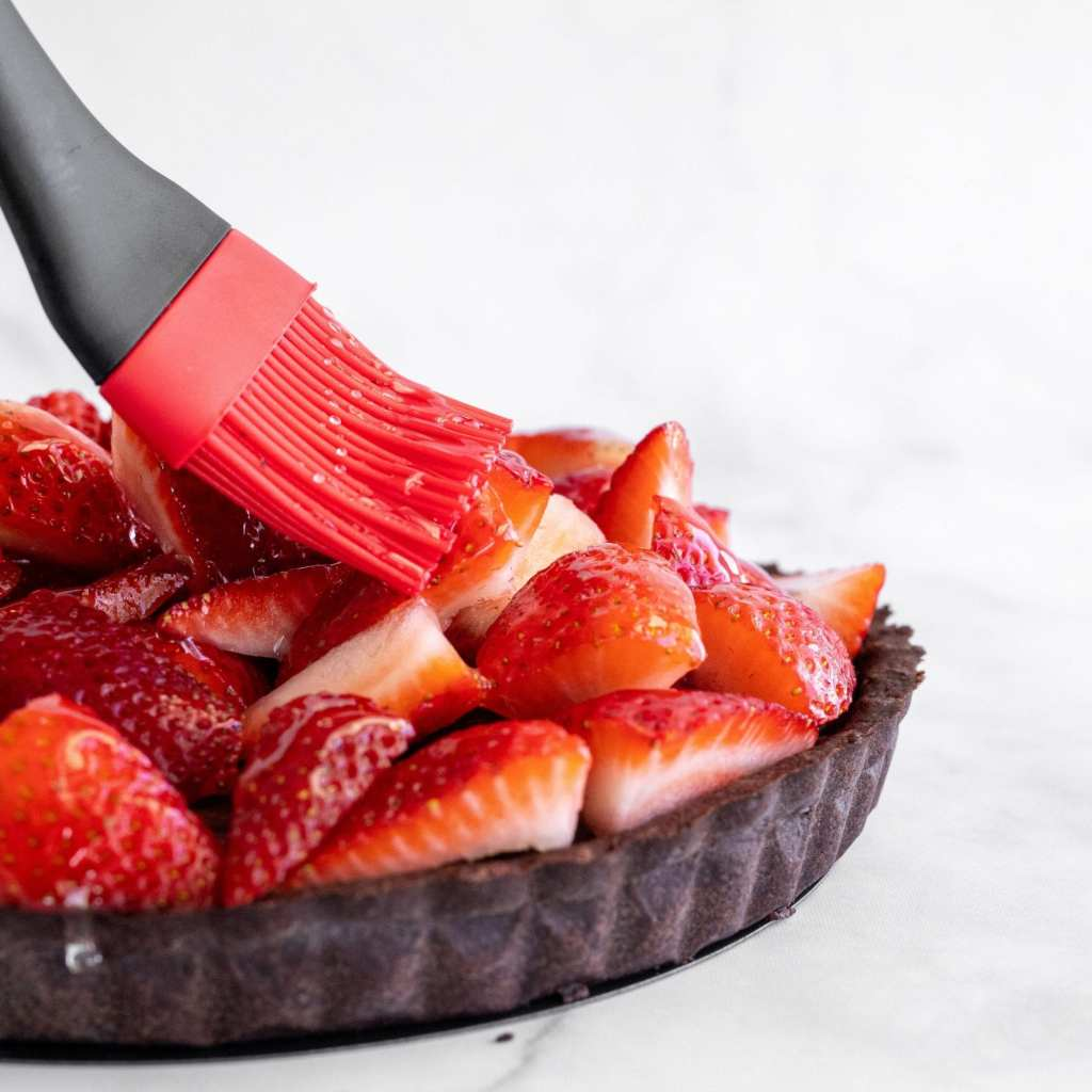 brushing quartered strawberries with a silicone pastry brush