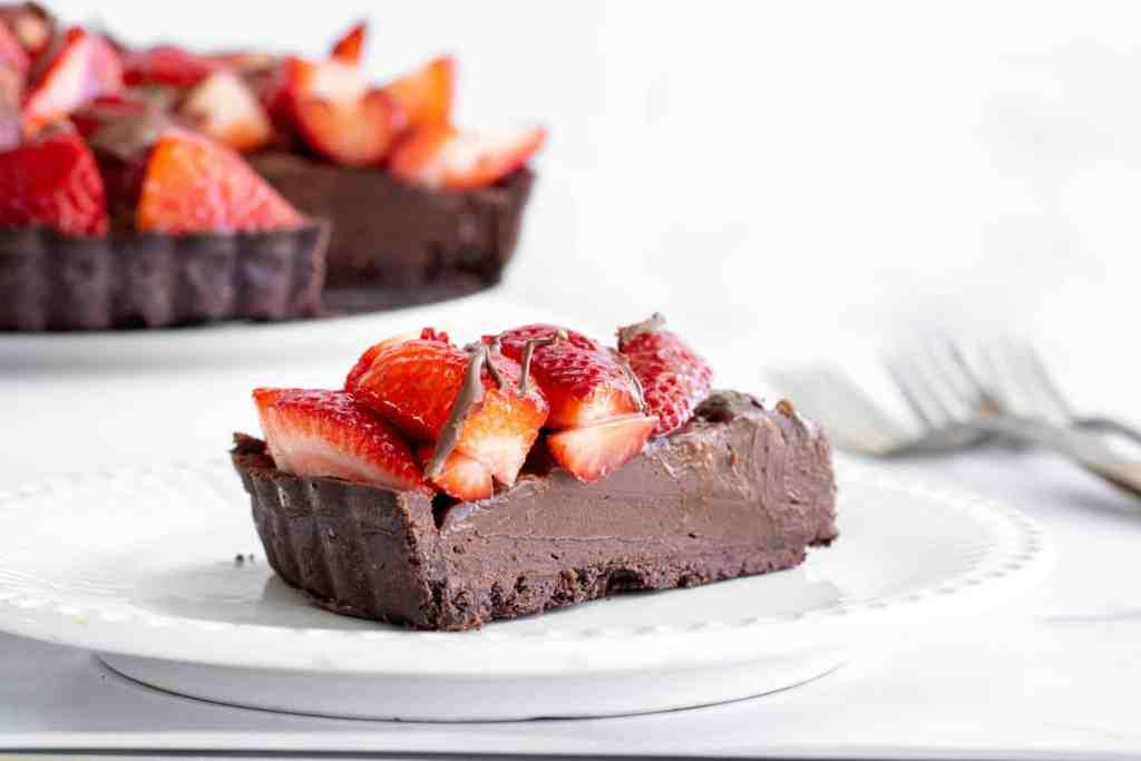 slice of dark chocolate strawberry tart on white plate.