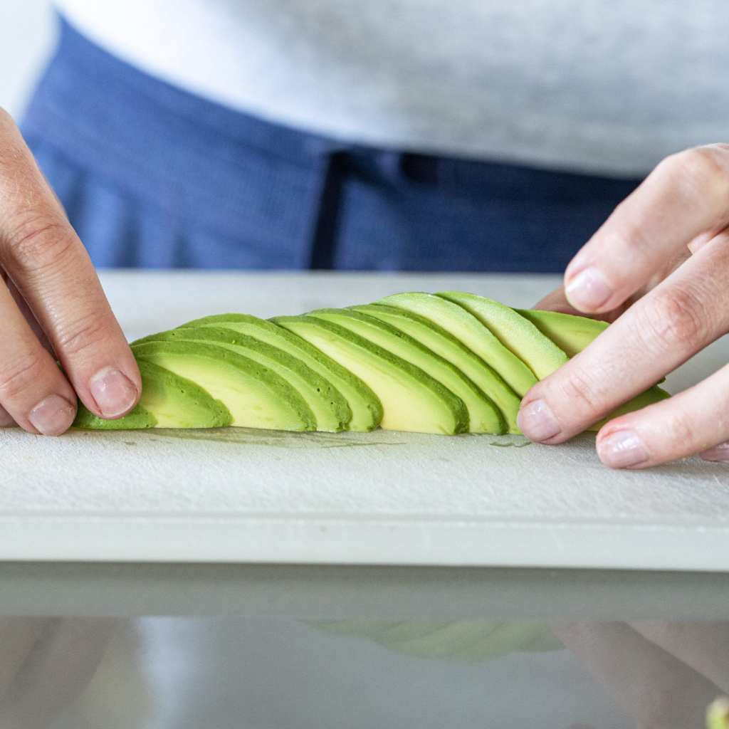 woman fanning out avocado slices to form a avocado rosette on plastic cutting board.