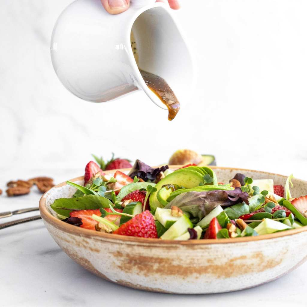 pouring a balsamic poppyseed dressing over a green salad with strawberries, pecans, cucumbers and microgreens