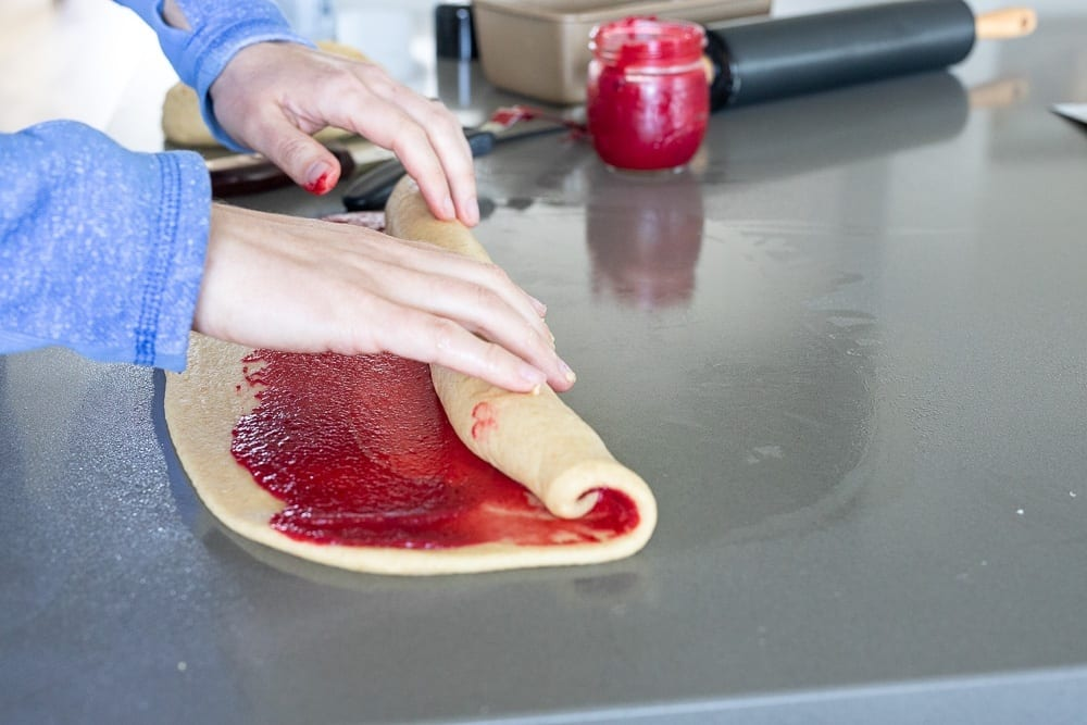 side view of woman rolling raspberry swirl loaf on counter top