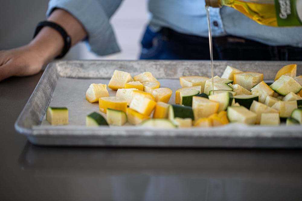 woman drizzling olive oil over cubes veggies for roasting in metal sheet pan