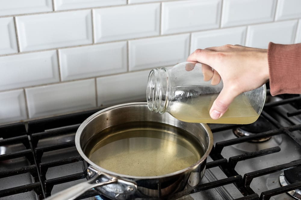 pouring vegetable stock from a mason jar into a stainless steel pan, preparing the rice for a blackened halibut bowl